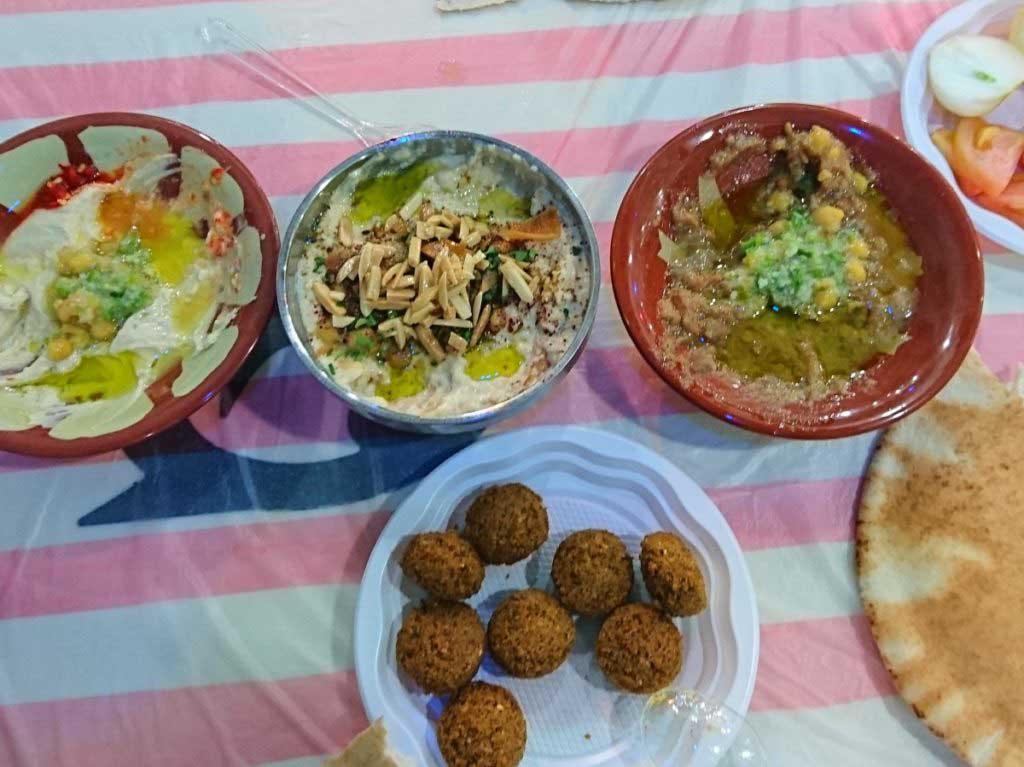 Jordanien, Amman, Falafel und Hummus auf Plastiktischdecke. Geldsparen in Jordanien, günstig aber gut essen.