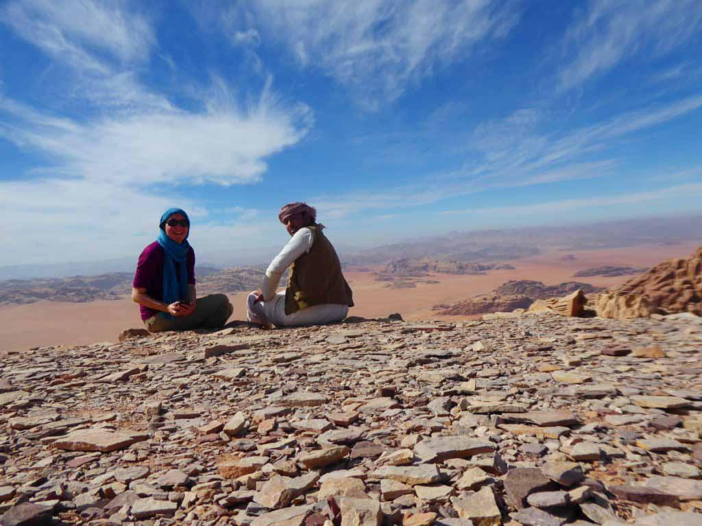 Wandern im Wadi Rum, Guide und Frau sitzten auf dem Boden vor spektakulärer Aussicht über das Tal hinter ihnen. Wissenswertes in Jordanien, sprechen die Menschen dort Englisch
