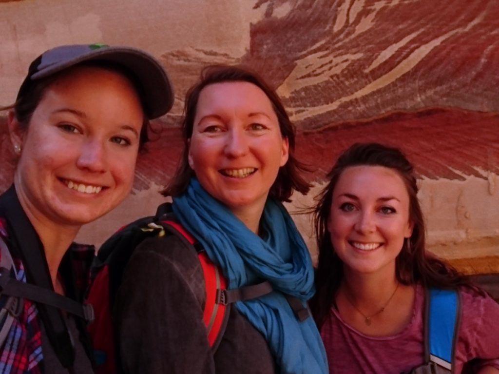Wissenswertes Jordanien, Sicherheit in Jordanien, Wandern in der Gruppe. 3 Frauen lächeln in die Kamera vor marmorierten Steinen in Petra, Jordanien
