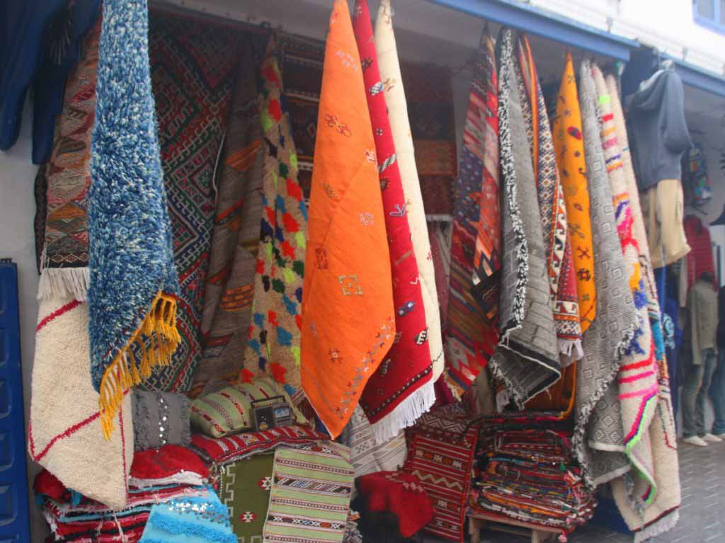 colourful carpets hanging in shop in Morocco, best souvenirs in Morocco