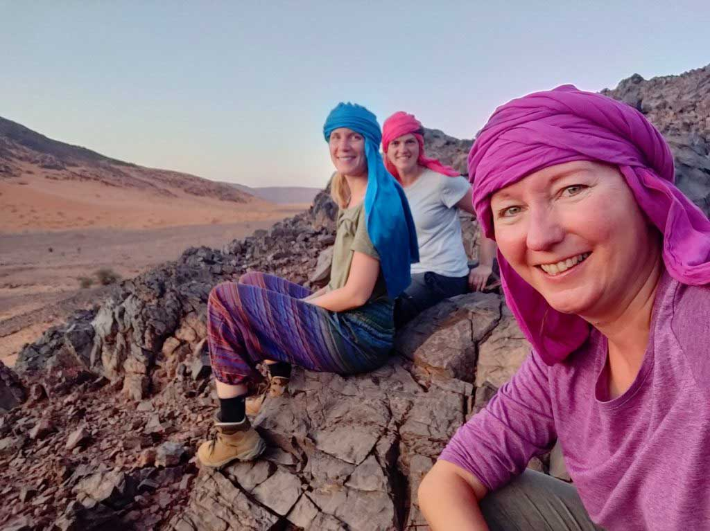 Women sitting on a mountain in the desert at sunset