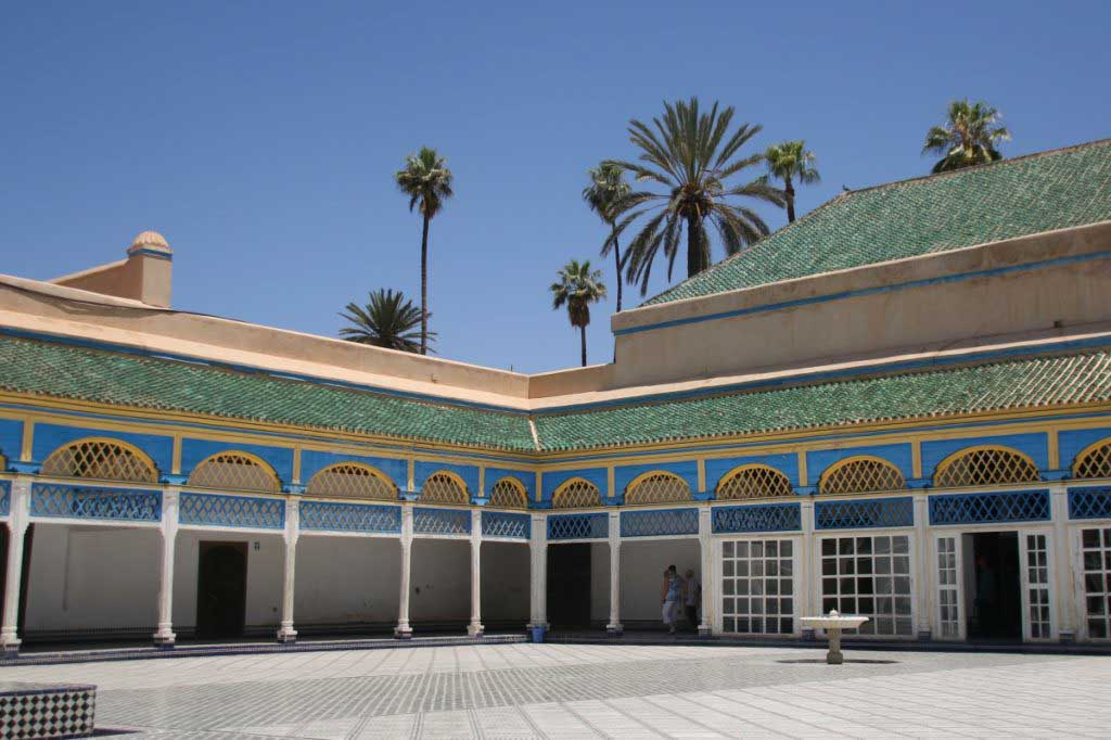 Bahia Palace in Marrakesch. White tiled courtyart with water fountian. Surrounded by white columns, topped with blue arches and a green tiled roof. most beautiful place to visit in Morocco