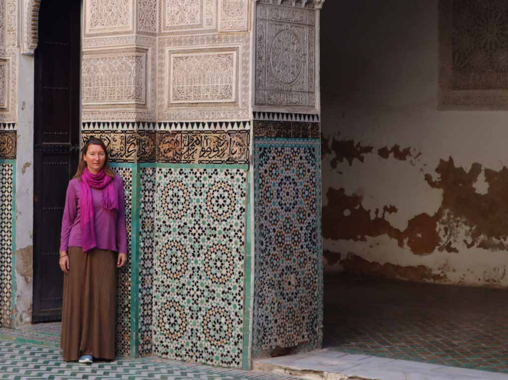 Women in long skirt and longsleeve shirt with pink scarf in front of tiled mosaic wall. What to wear in Fes, Morocco