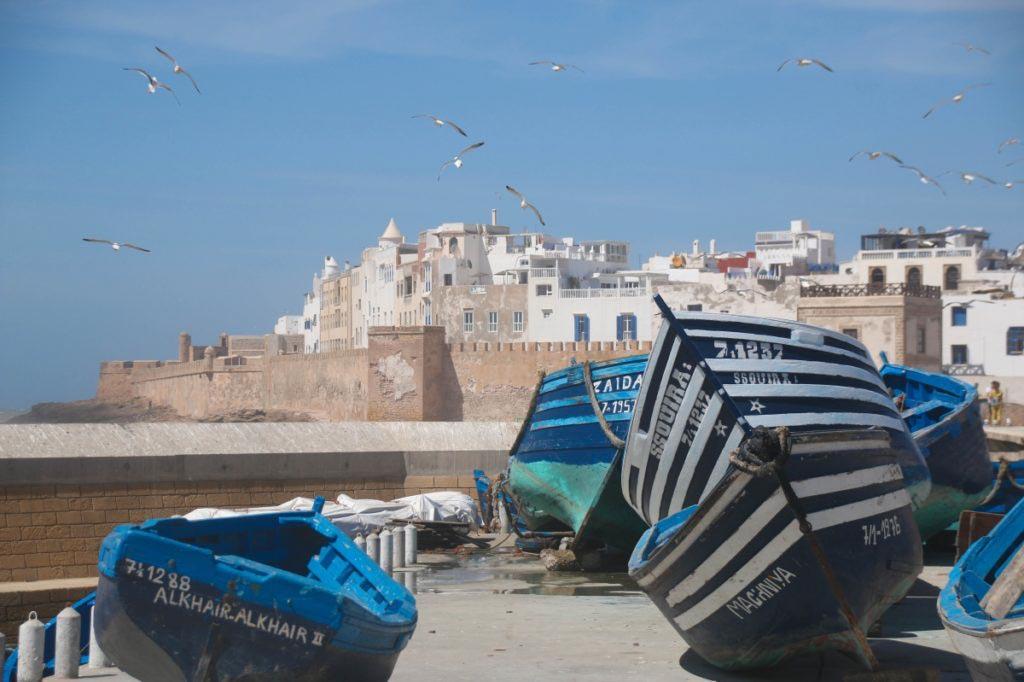 Medina von Essaouira, weiße Häuser hinter Stadtmauer am Meer. Im Vordergrund blau bemalte Fischerboote