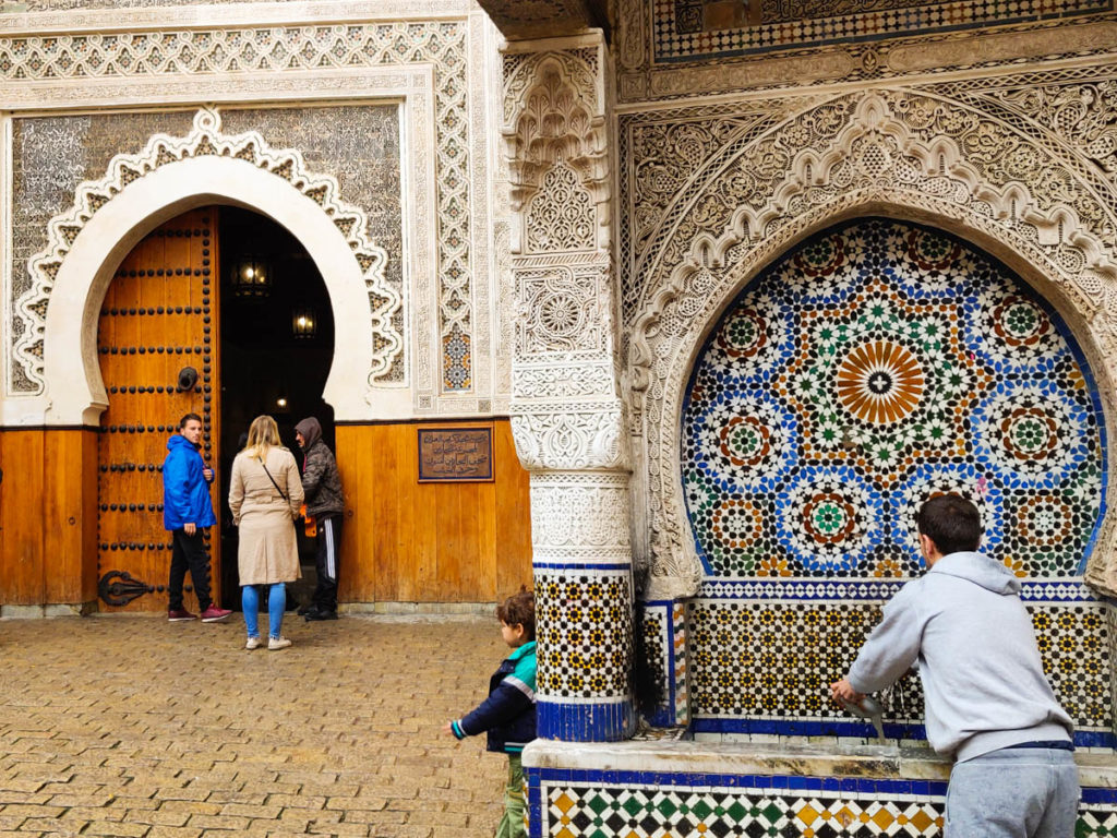 water fountain next to entrance to museum. people entering. boy drinking water. Fes travel guide