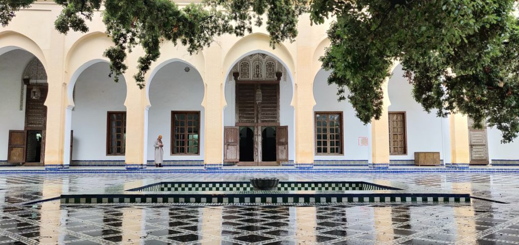 courtyard with fountain, man walking under arcades in the background. travel guide Fes