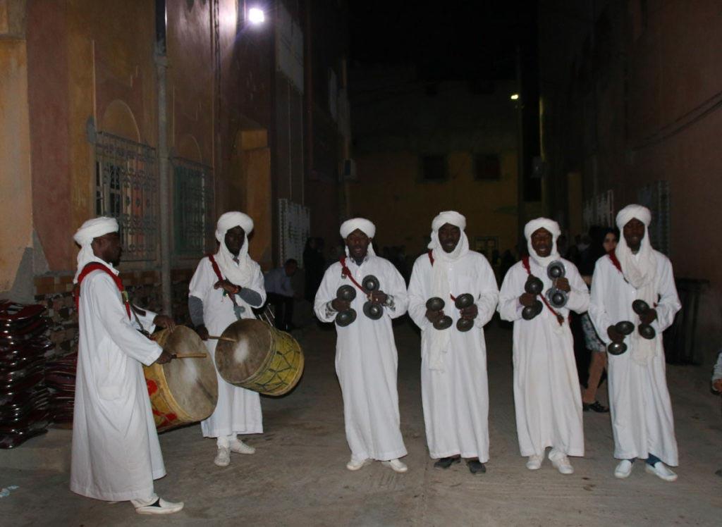 Weiß gekleidete Männer mit Musikinstrumenten auf der Straße