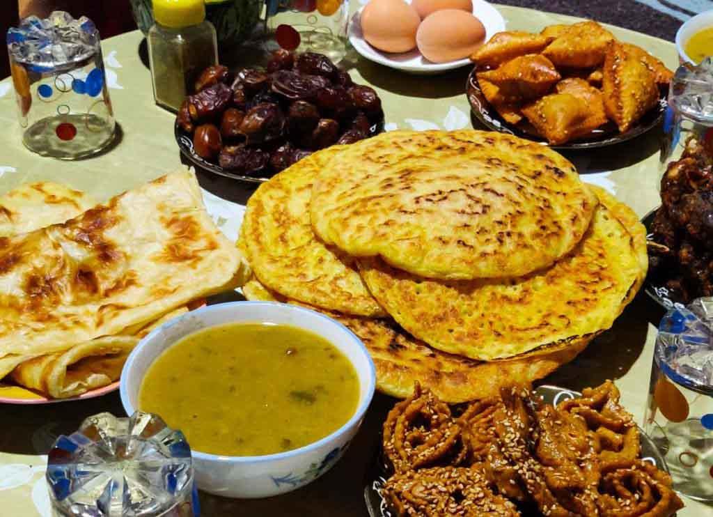 Crepes, Fladenbrot, Suppe, Kekse, Datteln und gekochte Eier auf dem Tisch fürs Fastenbrechen im Ramadan