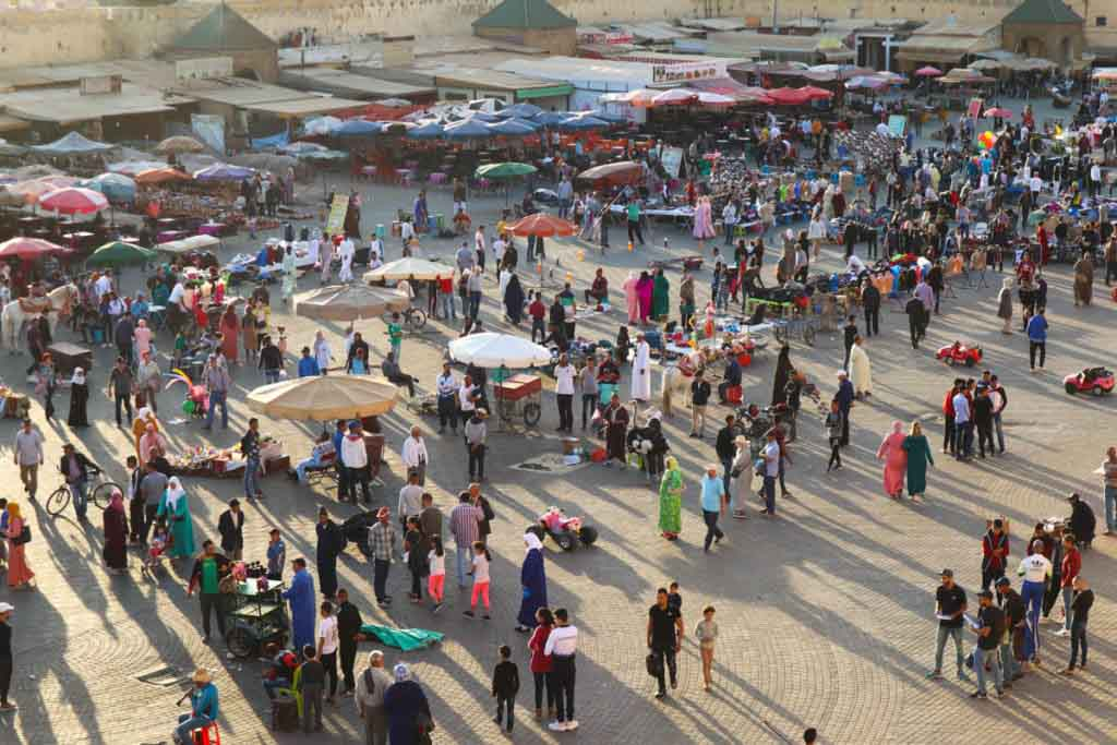 Square full of people and umbrellas in the afternoon sun. Place el hedim, Meknes