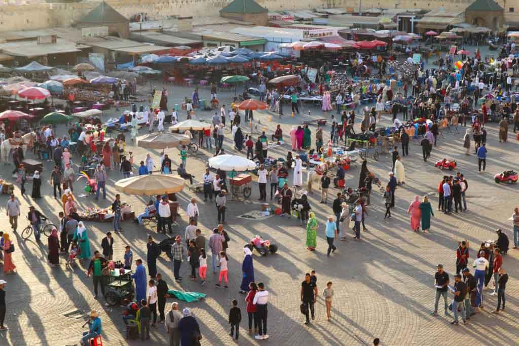viele Menschen auf Platz mit Sonnenschirmen, Saftständen und Verkäufern, Place el Hedim in Meknes, Meknes Reiseführer