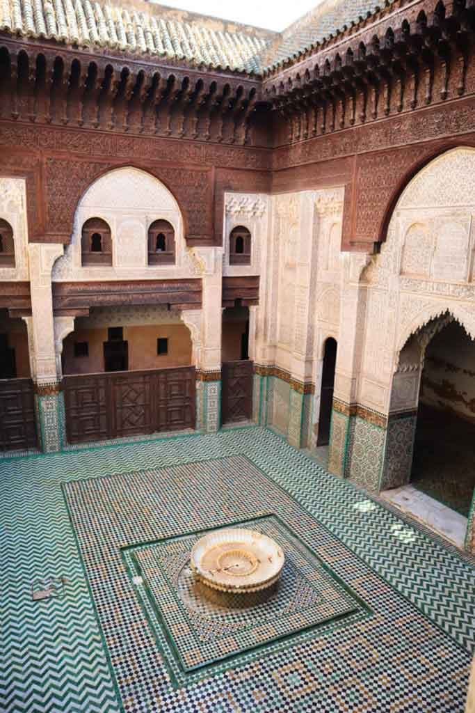Tiled courtyard with fountain in the middle. The walls are intricately decorated with stucco and carved cedar wood. Medersa Bou Inania, travel guide Meknes