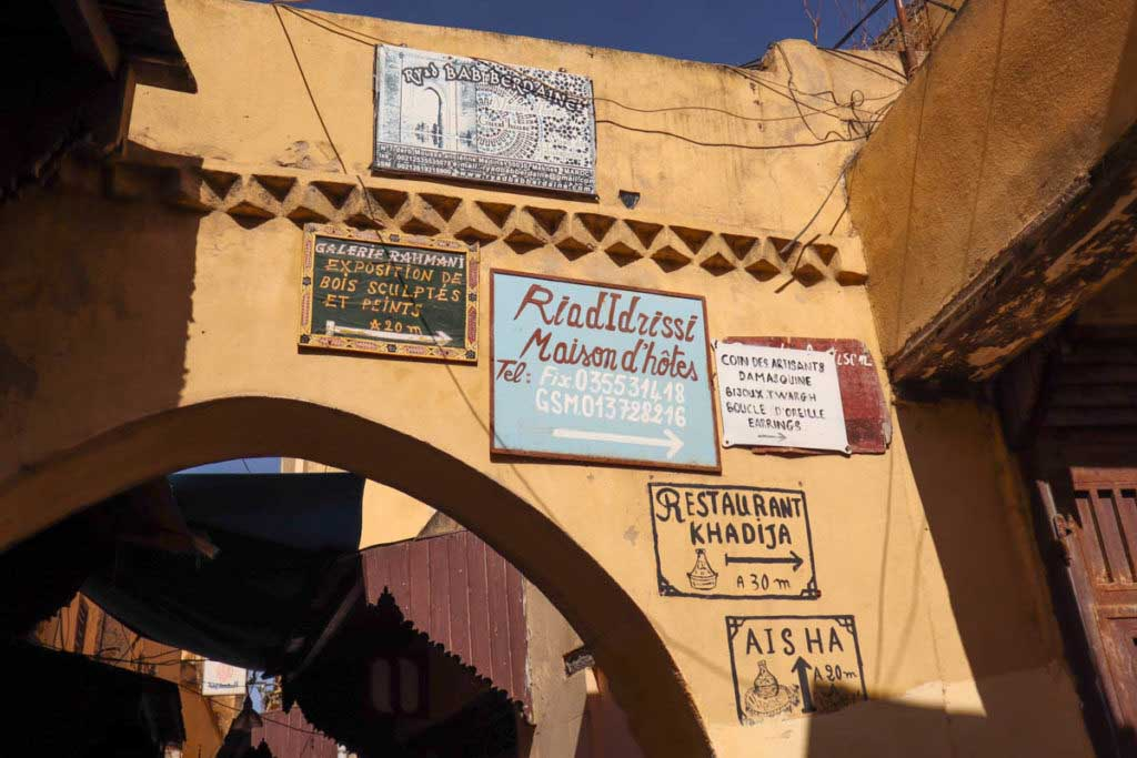 signs on a wall pointing to riads and restaurants in the medina of Meknes