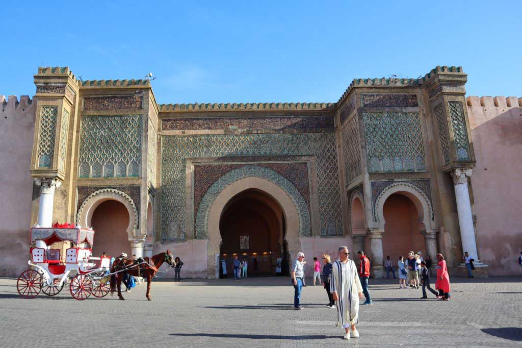 Big city gate in Meknes, one of the imperial cities of Morocco, people crossing the street, a horse and carriage waiting for customers