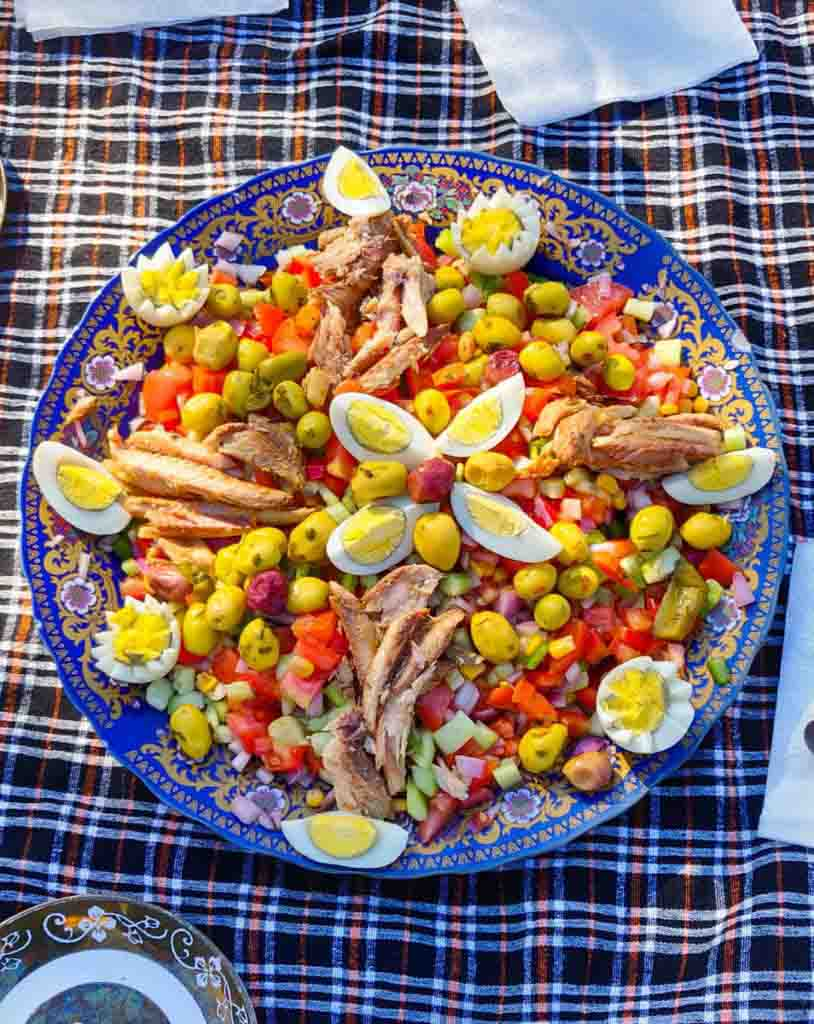 Colourful Moroccan salad with tomatoes, cucumber, onions, olives, boiled eggs, canned makarel and dressing. All on blue plate with gold pattern on a picnic blanket