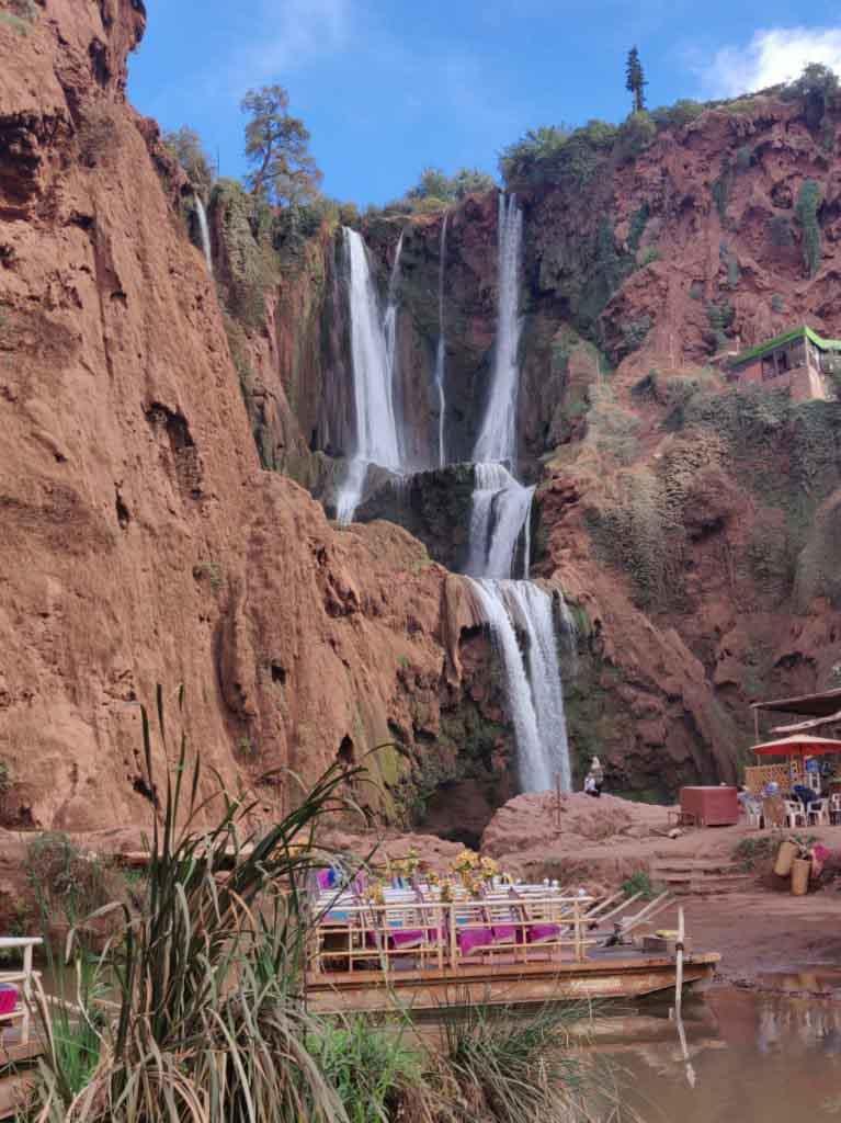 Wasserfall über mehrere Etagen. rötlich-braunes Gestein mit etwas grünem Bewuchs. Ouzoud Wasserfälle, beliebtes Ausflugsziel und Topsehenswürdigkeit in der Umgebung von Marrakesch in Marokko