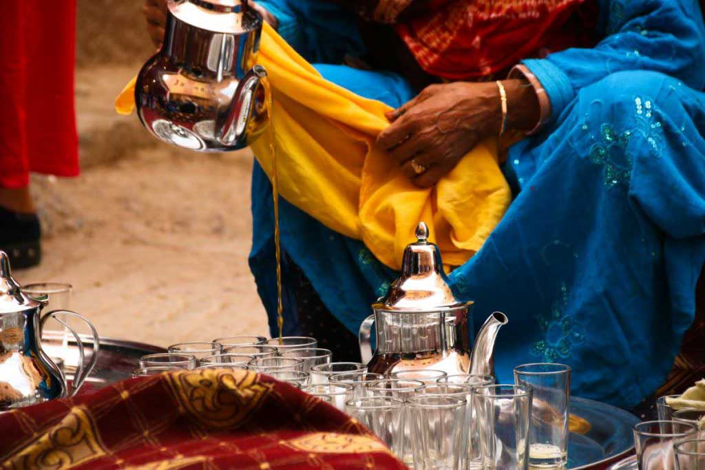 Woman in traditional Moroccan clothes pouring tea from silver teapot into small glasses