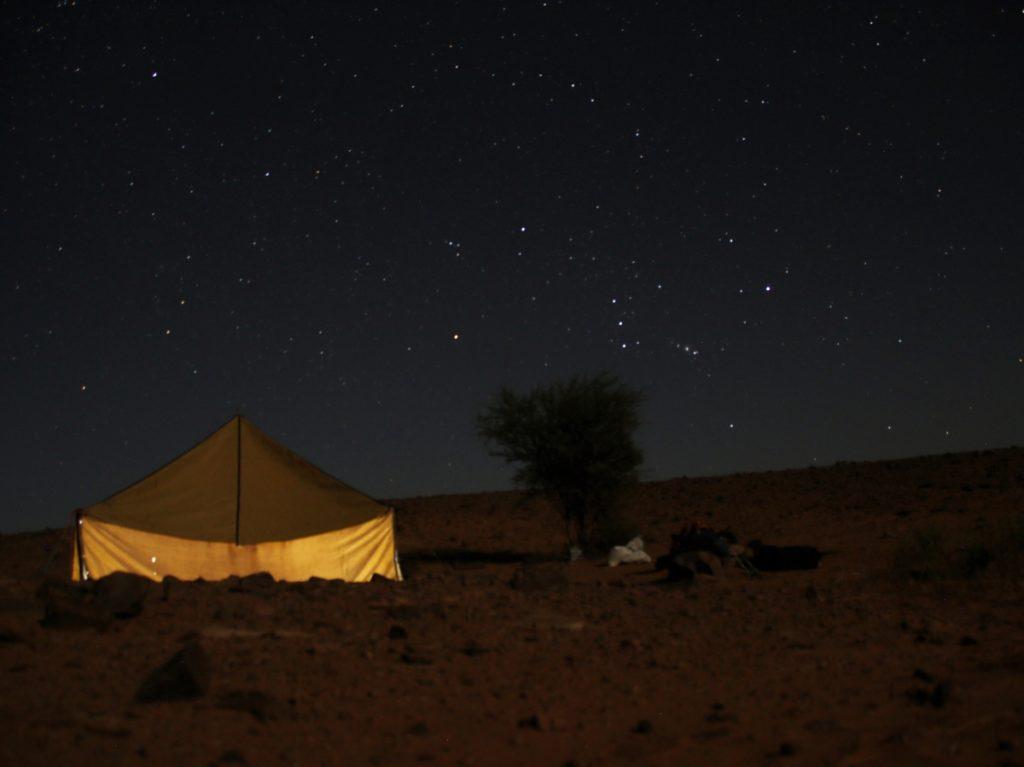 Beleuchtetes Zelt nebem Busch unter Sternenhimmel. Orion. Sternegucken ist ein Grund Marokko zu besuchen und zu lieben