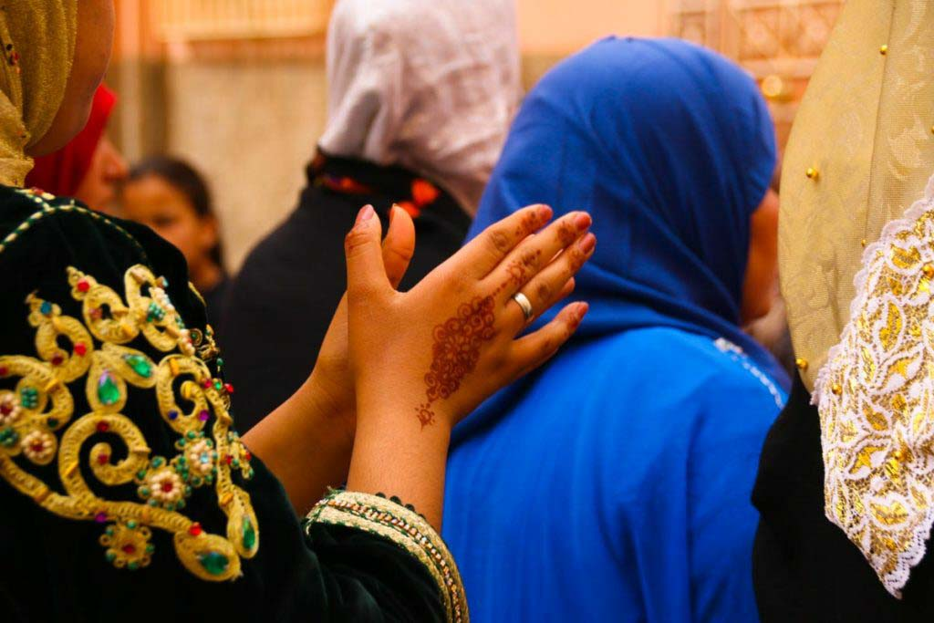 Women in traditional Moroccan clothes, hands painted with henna