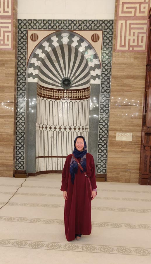 Woman in red cloak and blue scarf around her head in the Al Fateh Mosque in Bahrain. Behind her is the tiled prayer niche.