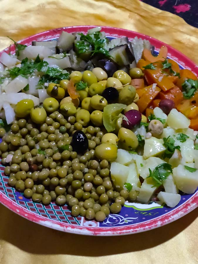 Traditional Moroccan food, cooked salad with potatoes, peas, olives, carrots, beets, aubergine and dressing.