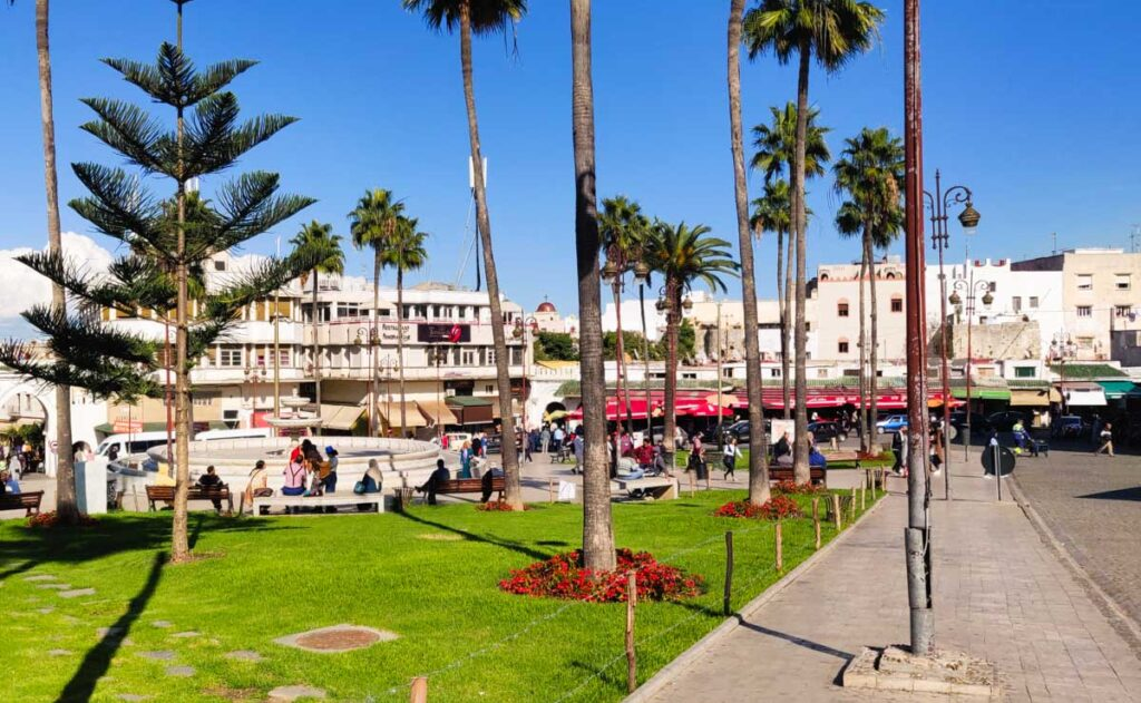 City square with grass, fountain with people sitting around it, palm trees, surrounded by white houses. Grand Socco in Tangier