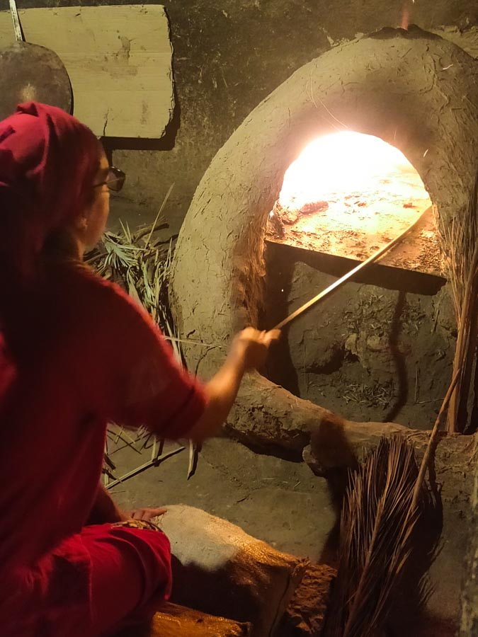 Moroccan woman infront of traditional clay oven baking bread