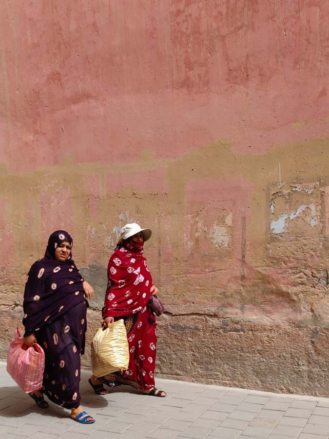 2 Moroccan women in traditional dresses walking along a wall
