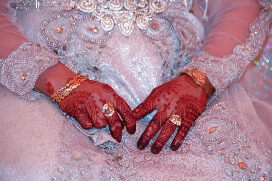 Hands decorated with traditional Moroccan henna tattoos. Wearing gold rings and armbands. Hands are on the lap of woman wearing white wedding dress with many gems