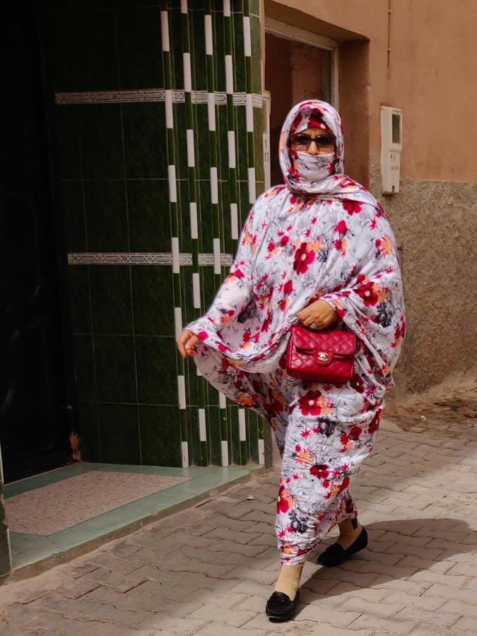 Moroccan woman in very stylish dress with matching headscarf, wearing sunglasses and red hand bag