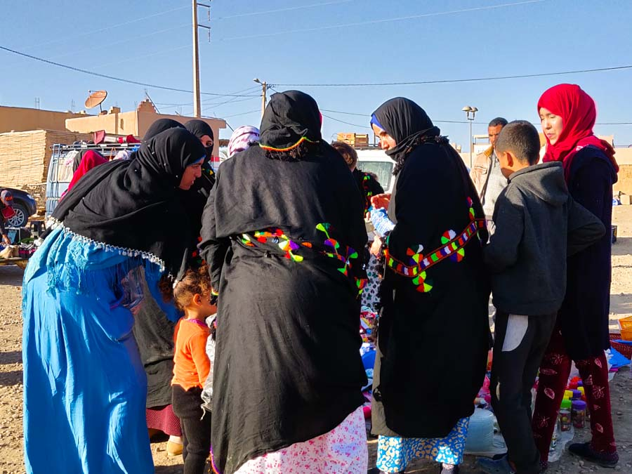 Women at market in black shawls with colourful decorations