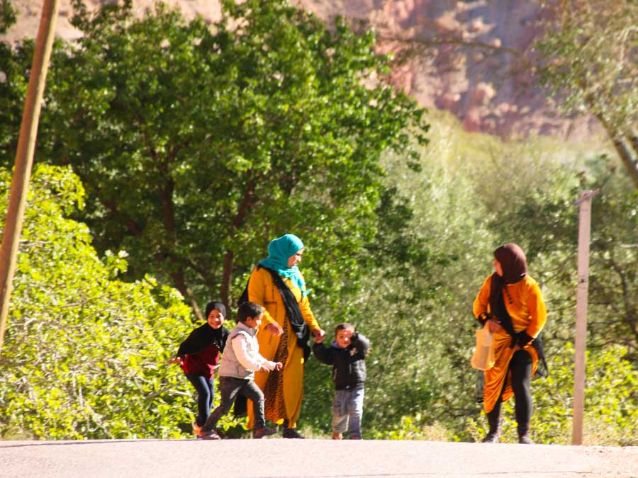 2 women with 3 children walking the street surrounded by trees. Women in Morocco