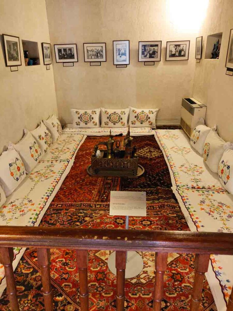 Room with red carpets surrounded by white cushions with colourful embroidery. Tea set in the middle of the carpet. In the front a wooden fence and a sign post describing the room