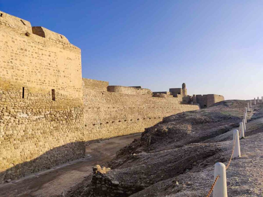 Huge stone walls of the Bahrain fort at sunset, one of the best things to do in Bahrain