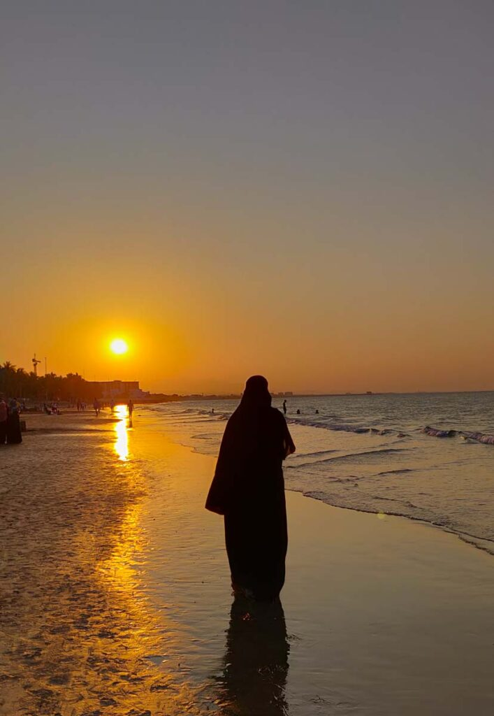 Women in abaya and hijab as silouette against the sunset at the beach