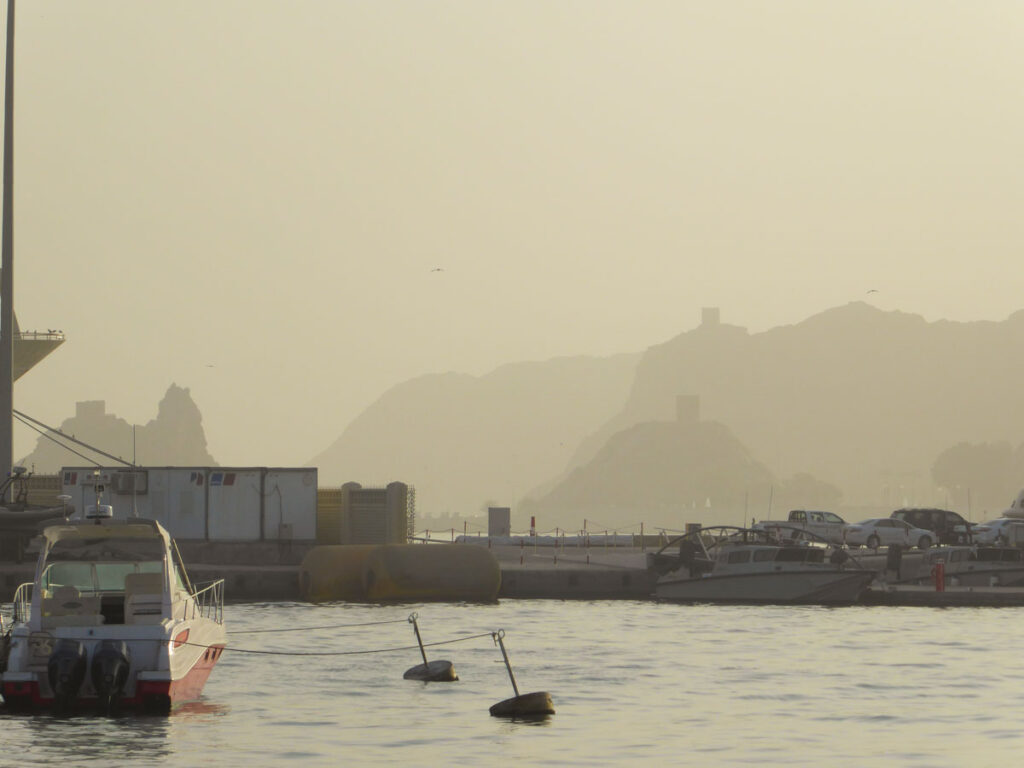 Misty view over the Muscat harbour, small boats on the front, mountains in the background