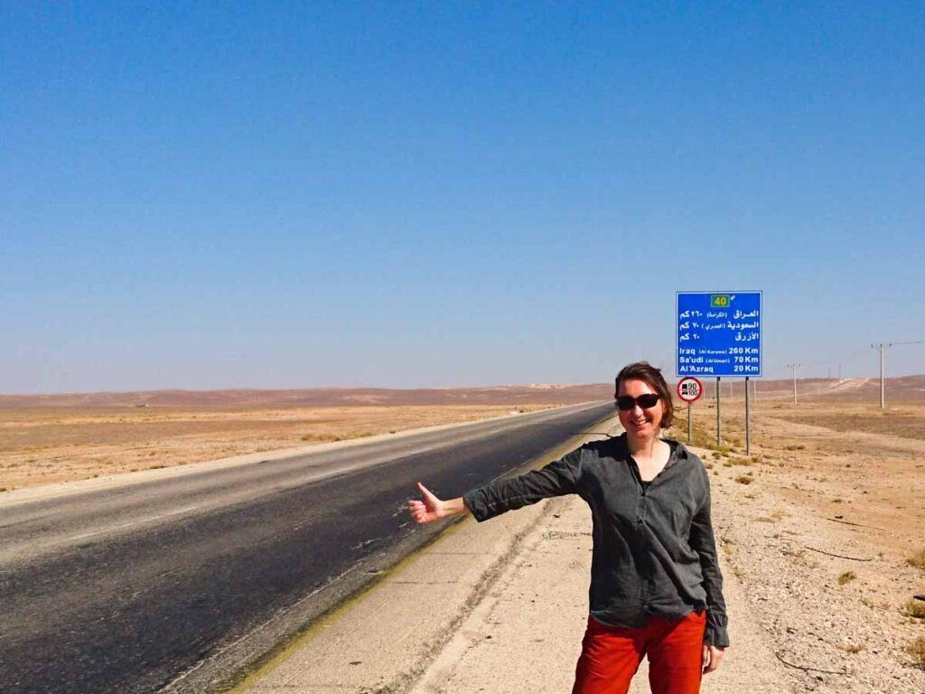 Woman in hitchhiking pose next to street in the desert. Sign with distances to Iraq, Saudi Arabia and city of Azraq in Jordan. Travel guide to Jordan