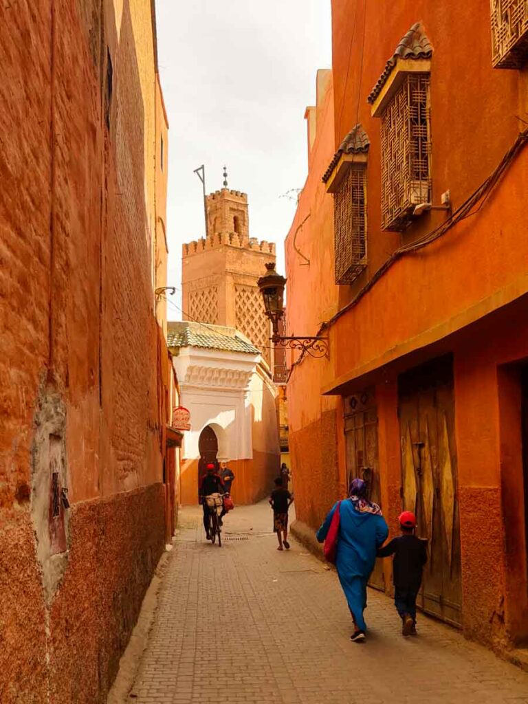 Orange houses on both sides of an alley, mosque in the background. people walking. what is a medina