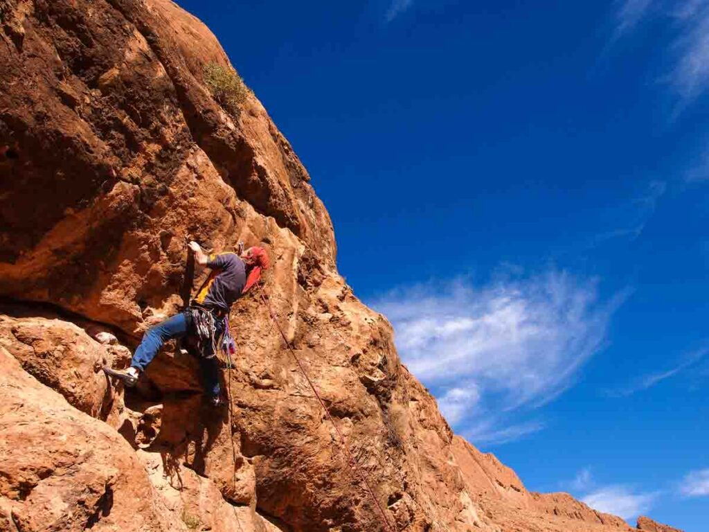rock climber on the rock face of the todra gorge in Morocco. climbing adventures in Morocco